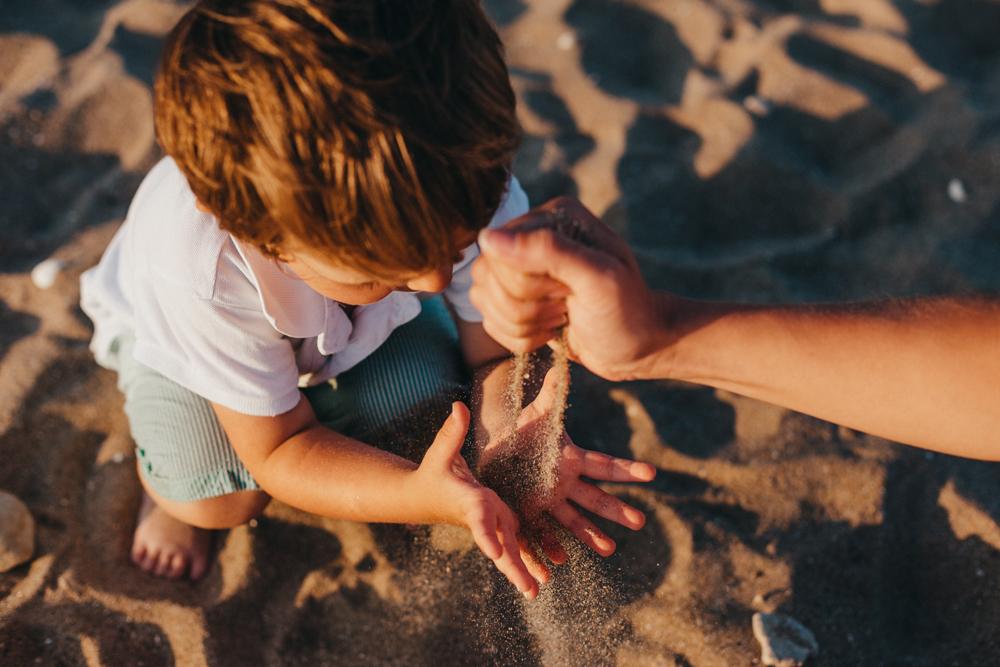 boy on Bamburgh beach playing with sand